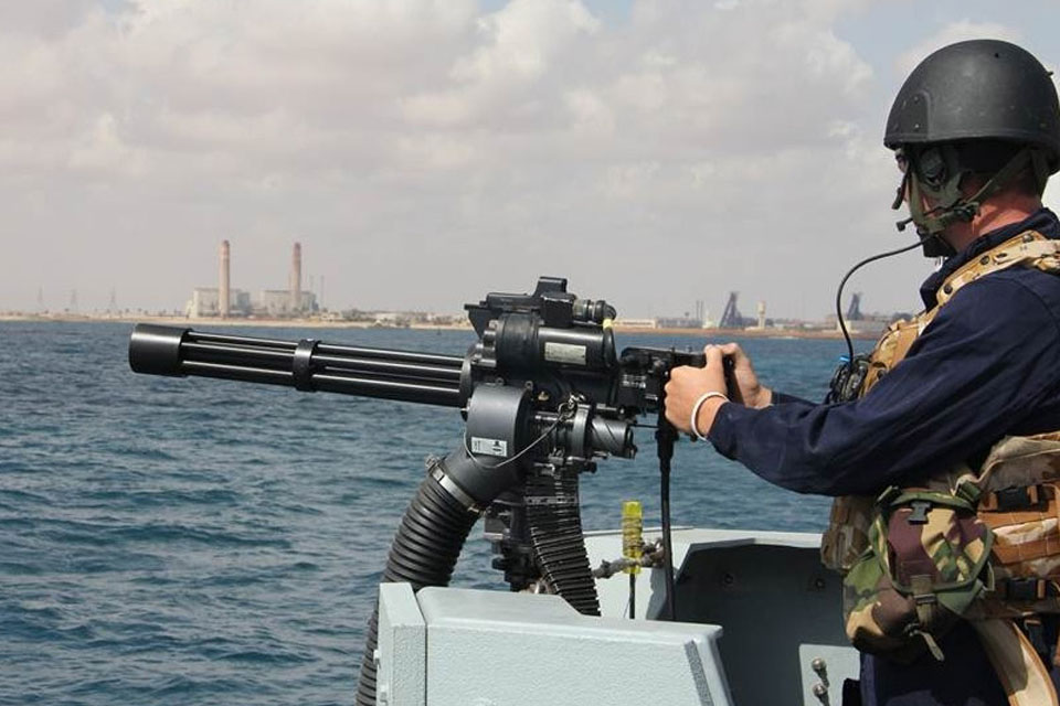 A sailor onboard HMS Bangor mounts the minigun