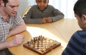 Children playing chess with man