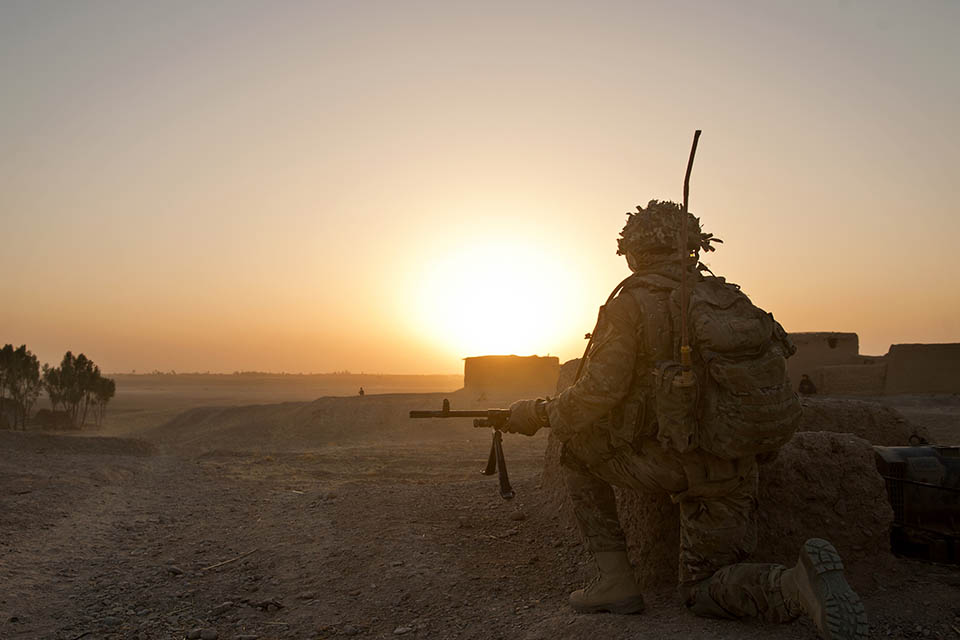 A soldier of 5 RIFLES kneels near the end of a patrol in Helmand, Afghanistan.