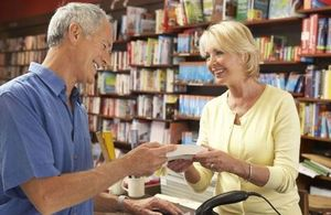 An image of a man buying a book from a woman assistant in a bookstore