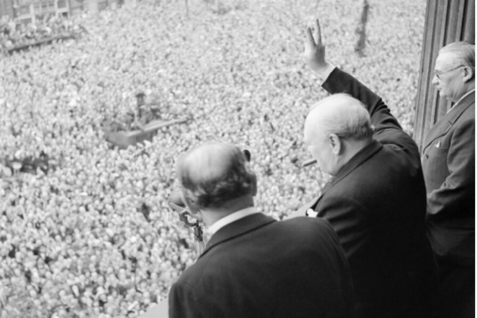 Winston Churchill waves to crowds in Whitehall on the day he broadcast to the nation that the war with Germany had been won, 8 May 1945 (VE Day). [Picture: Imperial War Museum H 41849]