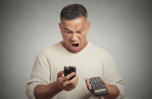 Man looking shocked after seeing mobile phone bill