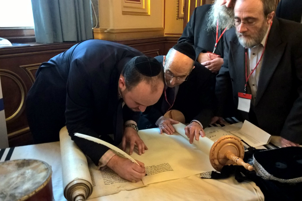 Jonny Daniels signing the scroll. With survivor, Bob Kirk (centre)