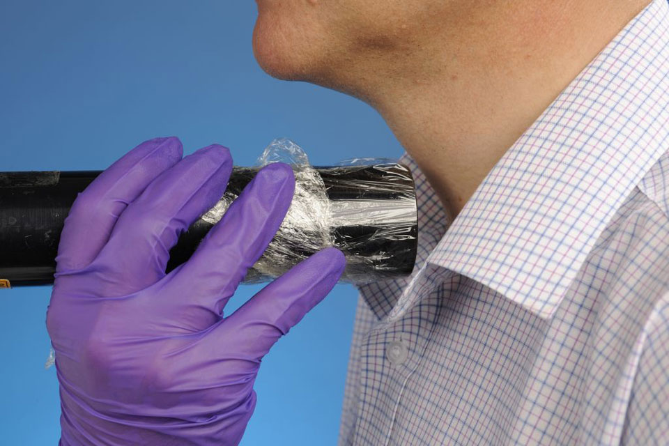 A hand wearing purple nitrile gloves holding a handheld detector close to a man's neck