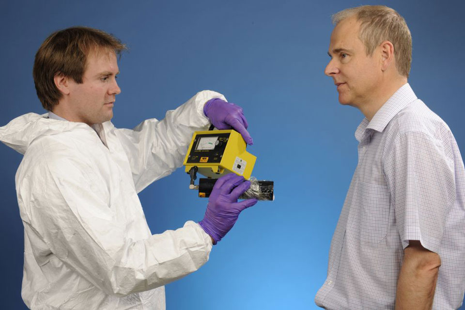 A lab technitian wearing a white lab suit and purple nitrile gloves holding a handheld detector 30 cm away from a man being monitored