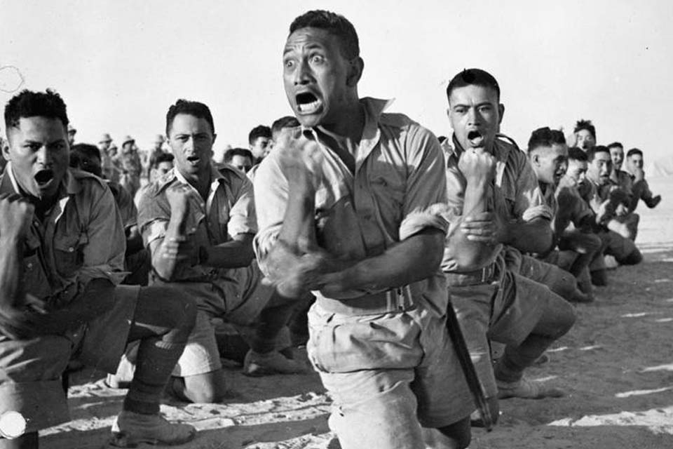 Maori troops perform the traditional 'Haka' during an inspection of the Auckland Infantry Battalion by King George of Greece, July 1941.