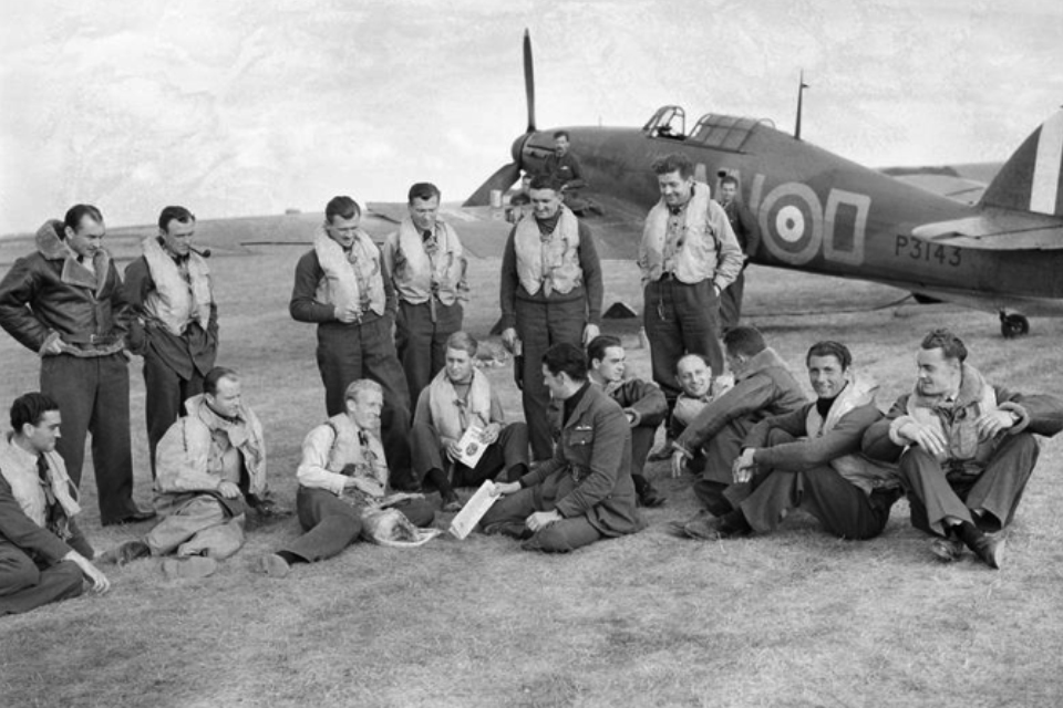 No. 310 (Czech) Squadron are grouped together informally. Most of the men are wearing their life jackets and a Spitfire is stationed in the background.