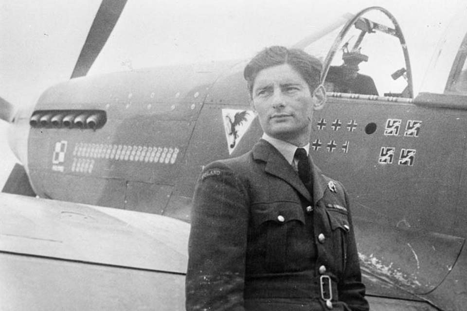 Squadron Leader Eugeniusz Horbaczewski of No. 315 Polish Fighter Squadron, standing by his new Mustang Mark III (FB387, PK-G) at Brenzett, Kent. The number of 'kills' of enemy planes is shown on the fuselage.