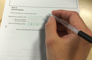 Graphic showing a hand holding a pen and filling an RLE1 form