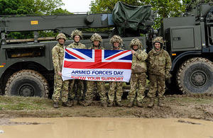 Soldiers next to Armed Forces Day flag