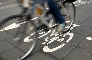 An image of a person cycling on a pavement