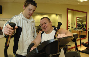 Teenage boy on a gym machine and a male trainer showing him what to do