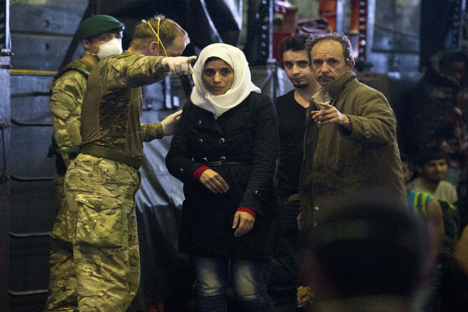 Migrants arrive on HMS Bulwark having been rescued by the Royal Navy in the Mediterranean