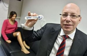 Bernard Ross, CEO of Sky Medical, holding up to camera a Geko medical device. Female patient in the background.