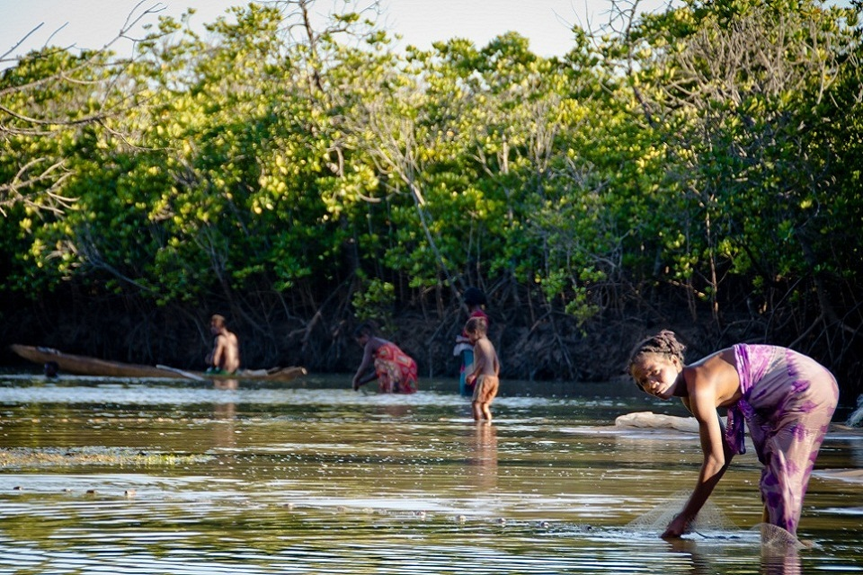 Men, women and children in water laying out fishing nets