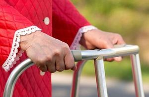 Close-up of older person's hands on walking frame