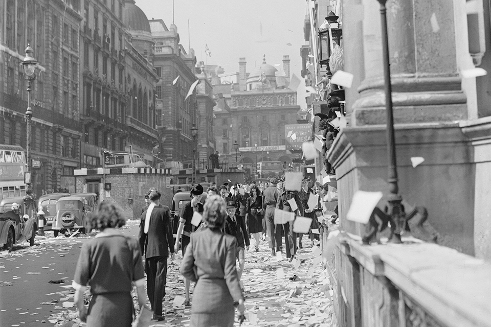 Civilians walk amongst the piles of torn up paper which have been thrown, 'ticker tape'-style, from the windows of offices, on Lower Regent Street, London, to celebrate the signing of the Peace with Japan.