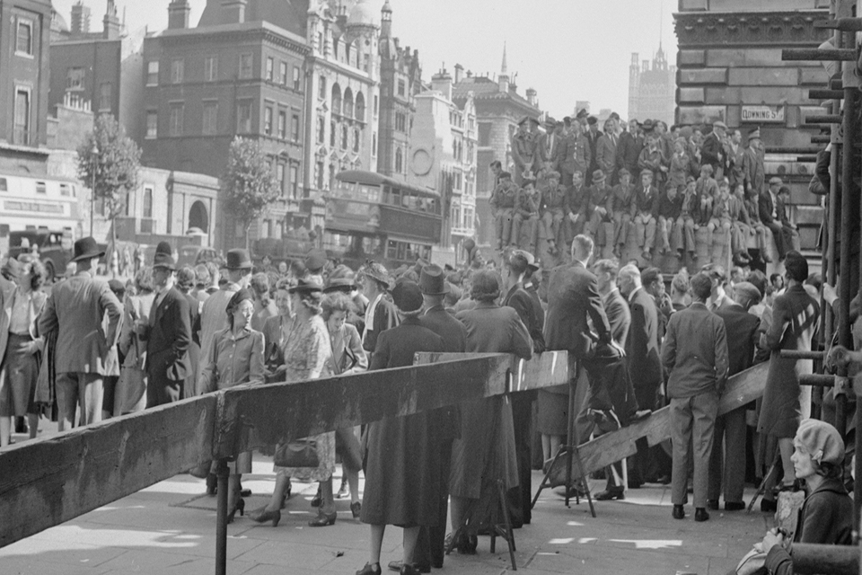 Crowds of people wait for news at the junction of Whitehall with Downing Street. The crowd consists of service personnel and civilians alike, all waiting for confirmation from the Prime Minister that the war in Japan is over.