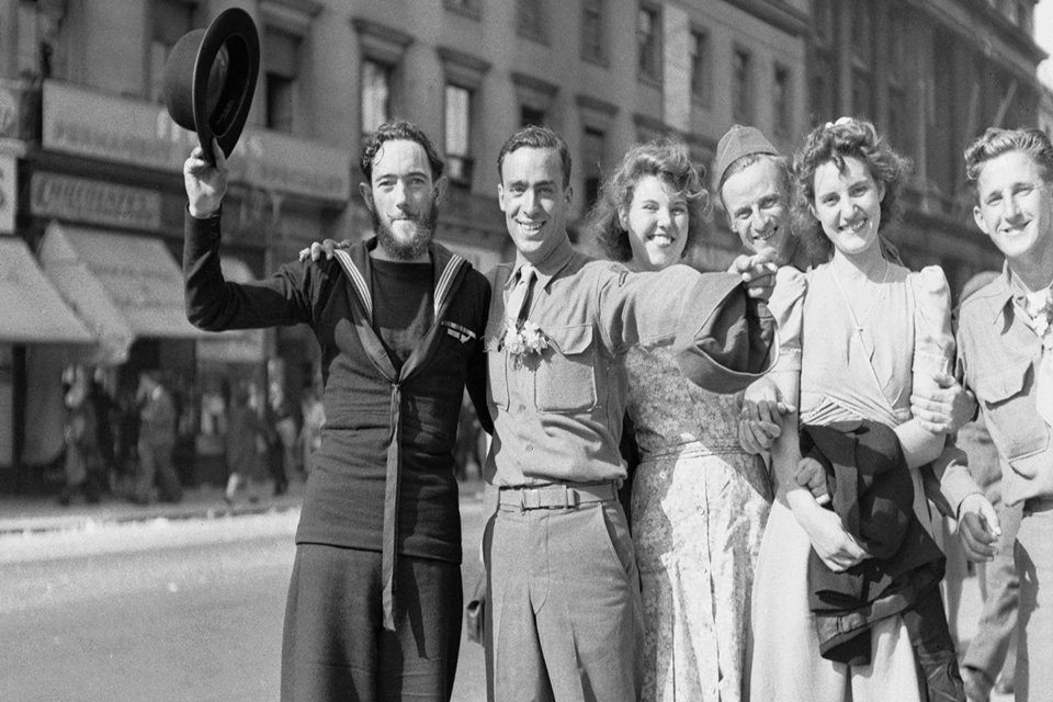 A New Zealand sailor raises his bowler hat in the sunshine after hearing of the Victory in Japan with several American soldiers and English civilian women on the Strand in London.