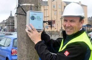 InTouch managing director John Walden holding up a monitoring device against a concrete lamp standard
