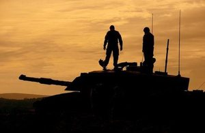 British Army reservists standing on a Challenger 2 tank, silhouetted against an orange sky
