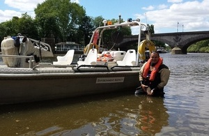 Environment Agency fisheries technical specialist, Tom Cousins, in the River Thames with a fish by the Environment Agency boat.