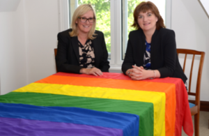 Image of Nicky Morgan MP and Caroline Dinenage MP with a rainbow flag