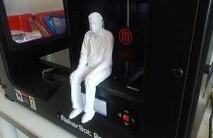 A 3d printed model of a man sitting on the edge of the 3d printer