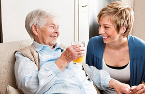 A carer spending time with an elderly woman