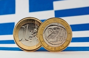 Image of the Greek flag and euro coins. [©istock.com/ikholwadia]