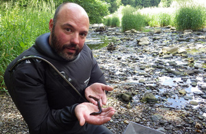 Environment Agency officer holding an eel