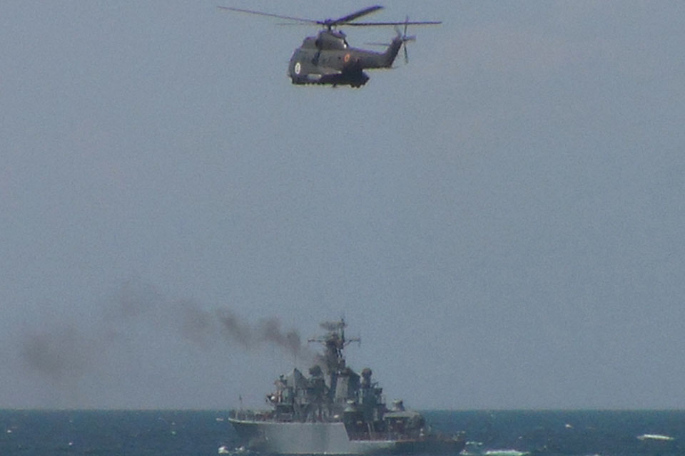 A Romanian helicopter flies over a Bulgarian minehunter as part of Exercise Poseidon