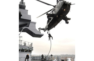 Royal Marines demonstrate a fast-rope attack from a Sea King helicopter onto the starboard bridge wing of HMS Bulwark