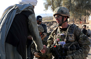 An Afghan elder greets a joint patrol of British soldiers and Afghan National Police in Lashkar Gah