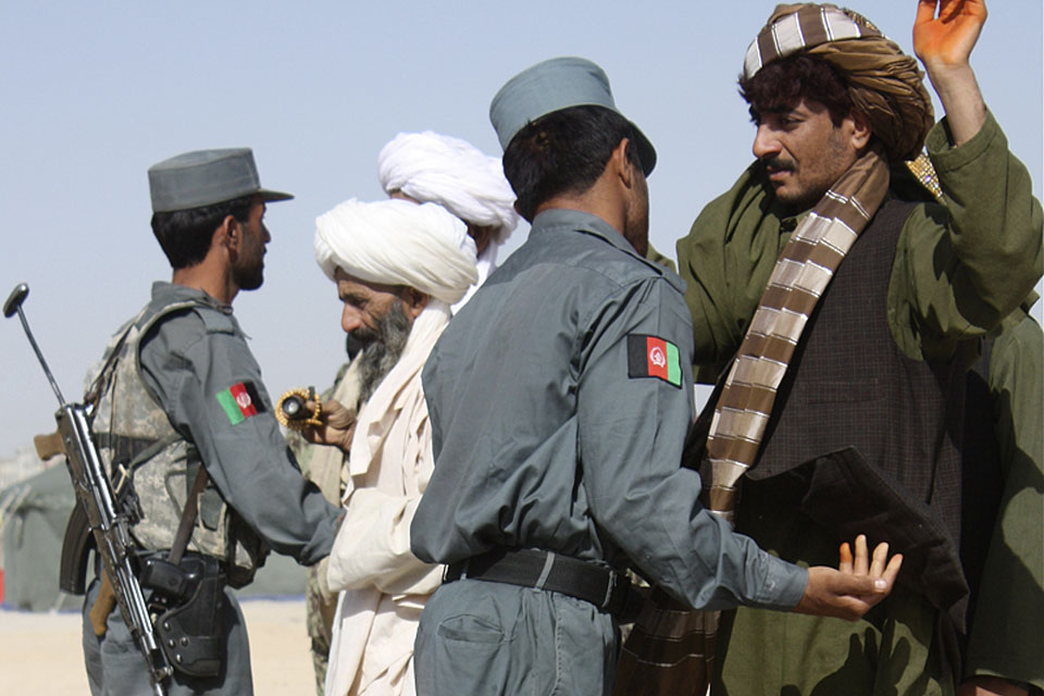 Afghan policemen carry out searches of members of the public (stock image)