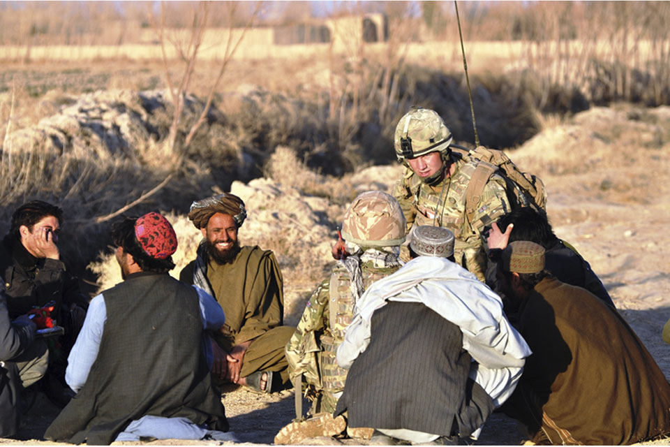 Corporal Jamie Williams speaks with Afghan men in Alokozi Shah, south of Popalzai Kalay, near Helmand's capital, Lashkar Gah