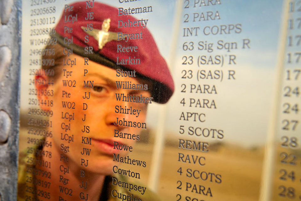 Musician Kate Whittaker reflected in the plaque on the Helmand Memorial Stone at Camp Bastion