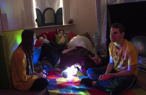 Children by lamp in darkened room
