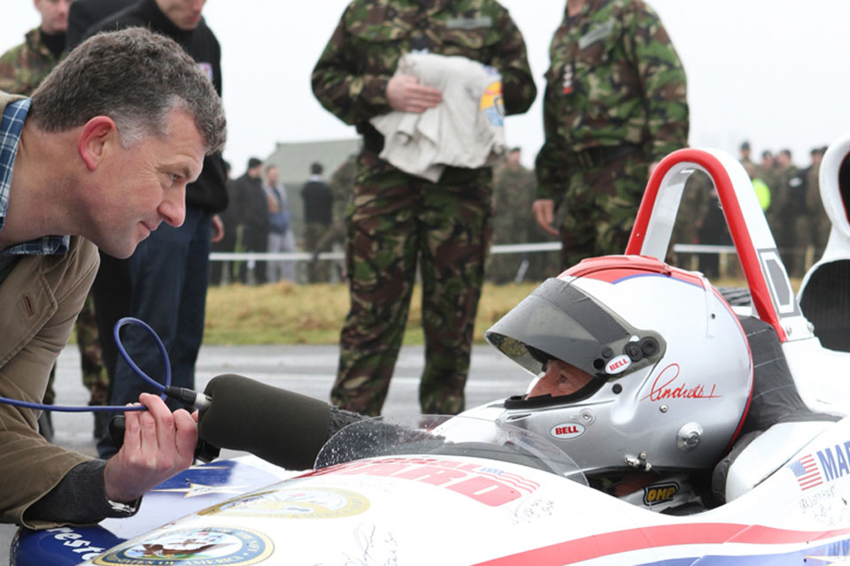Racing legend Mario Andretti at the wheel of his car at RAF Honington