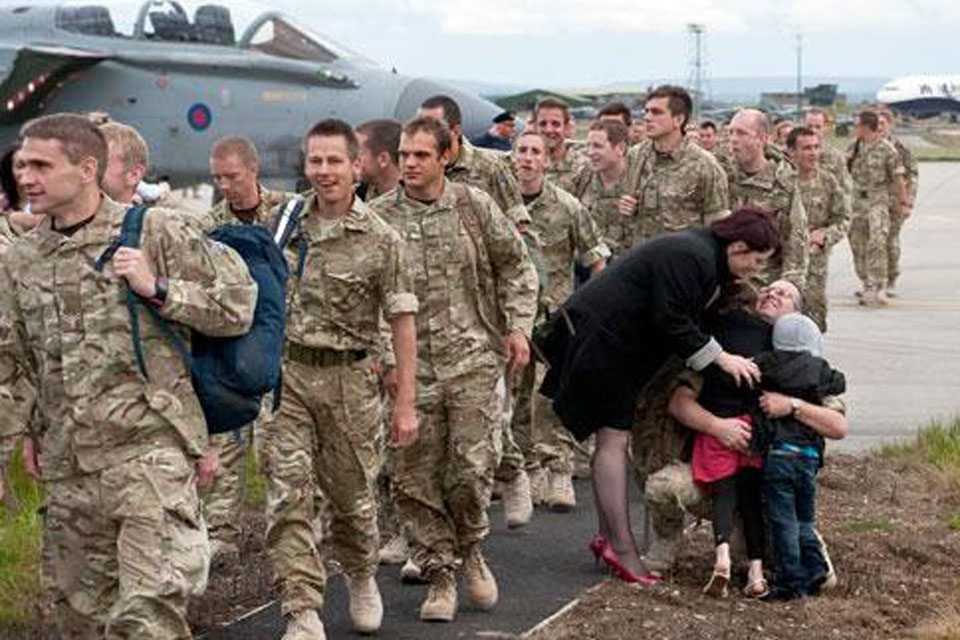 An airman from 617 Squadron gets a warm welcome home from his family