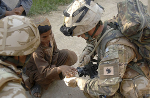 Lance Corporal McLoughlin cleans a cut on a local boy's hand with the water from his CamelBak drinking system