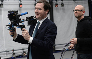 Chancellor holding a video camera in a filming studio