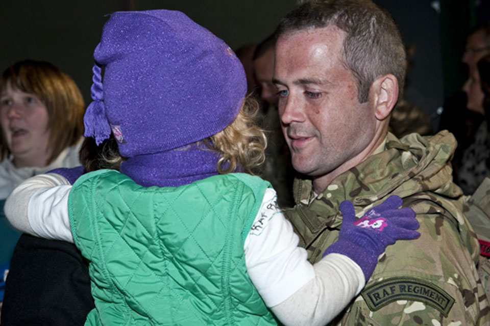 A gunner from 51 Squadron RAF Regiment holds his daughter at RAF Lossiemouth