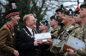 Provost Fergus Wood presents Corporal Robert Storrie of 5th Battalion The Royal Regiment of Scotland with a copy of the Freedom of the City Scroll. Looking on is Colonel of the Regiment, Lieutenant General Andrew Graham