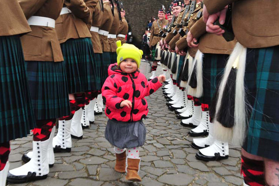 Two-year-old Hania Nowak from Poland 'inspects' the troops of the Royal Regiment of Scotland during her visit to Stirling Castle with her parents
