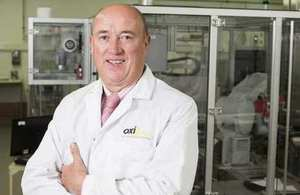 Chief executive Huw Hampson-Jones standing in white coat in OXIS Energy clean room