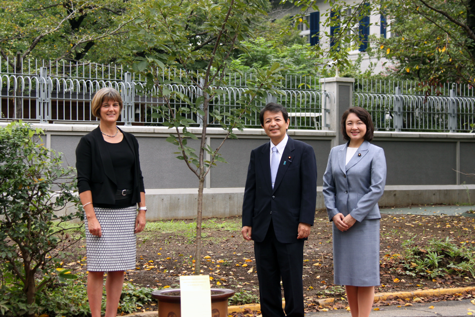 State Minister Miyashita and Chargé d'Affaires Longbottom posed for a photo with a taihaku cherry tree planted by HRH The Duke of Cambridge during his first visit to Japan in February 2015.
