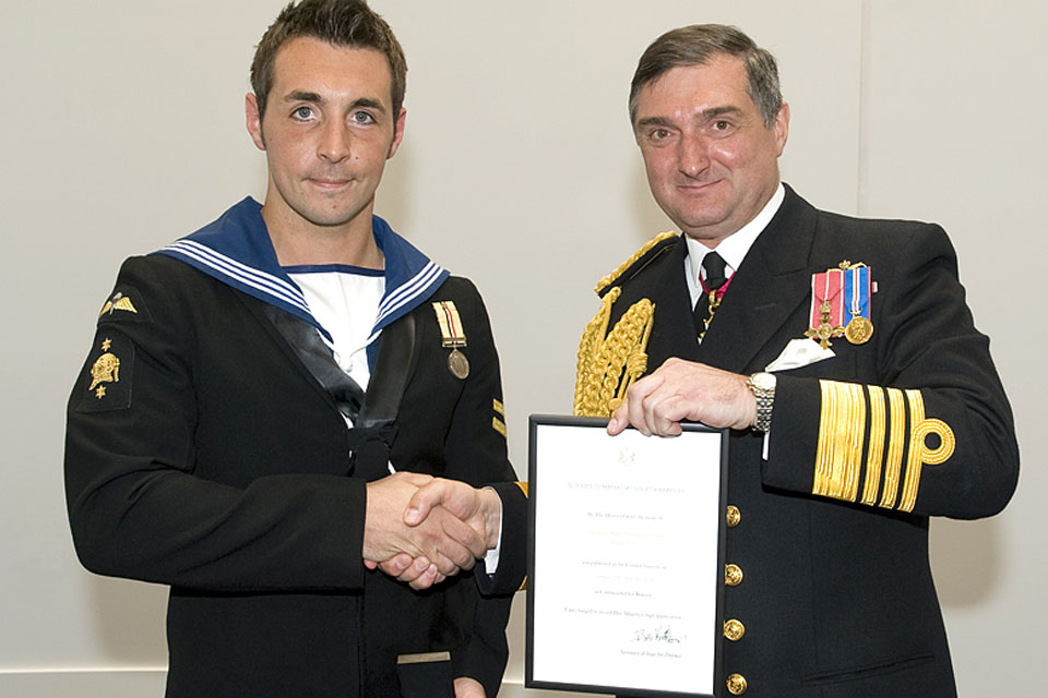 Admiral Sir Trevor Soar (right) presents the Queen's Commendation for Bravery to Leading Seaman (Diver) Carl Thomas