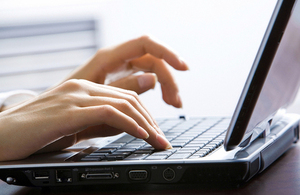 A person typing on a laptop computer.