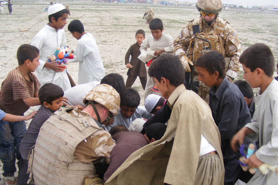 Supplies from an aid drop being distributed to children at Kujah Rawesh School in Kabul by Staff Sergeant John Stephenson of 2 Signal Regiment